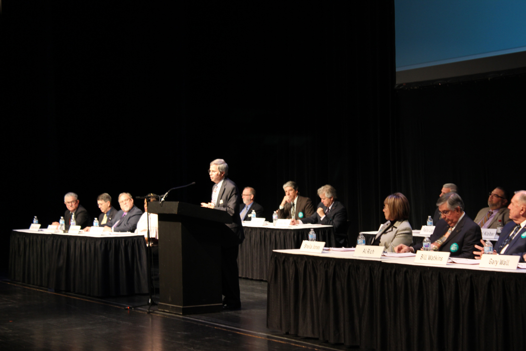 TFCU CEO Mike Kloiber speaking from stage at 2018 Annual Meeting with volunteer board sitting in the background.