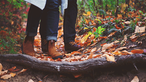 Close up of people walking on a leafy path in the fall.