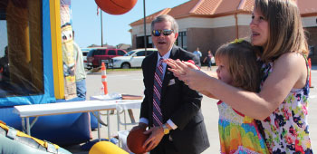Young girl playing a carnival game with TFCU President and CEO Michael Kloiber