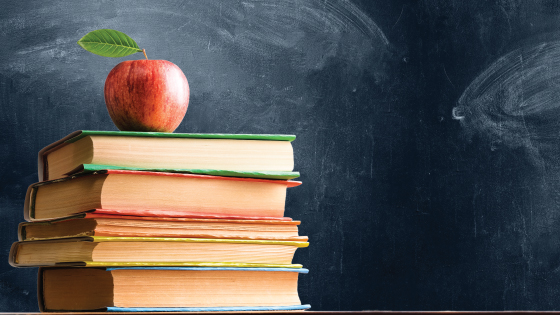 Apple sitting on stack of school books in front of chalkboard.