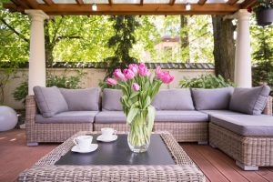 Outdoor living space featuring two white coffee cups and a vase of pink tulips sitting on top a wicker coffee table and surrounded by an L-shaped wicker couch with grey cushions.