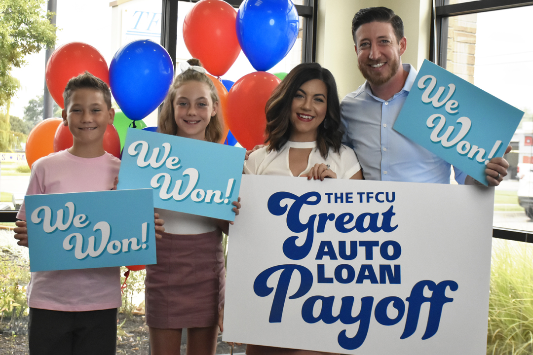 "The Mars Family, winners of The 2019 TFCU Great Auto Loan Payoff, holding ""We Won"" signs."