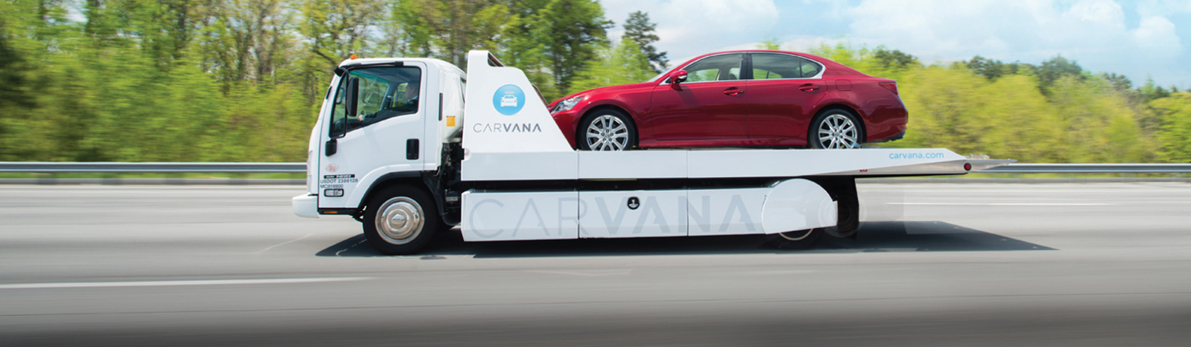 Carvana truck carrying a car to be delivered to a buyer