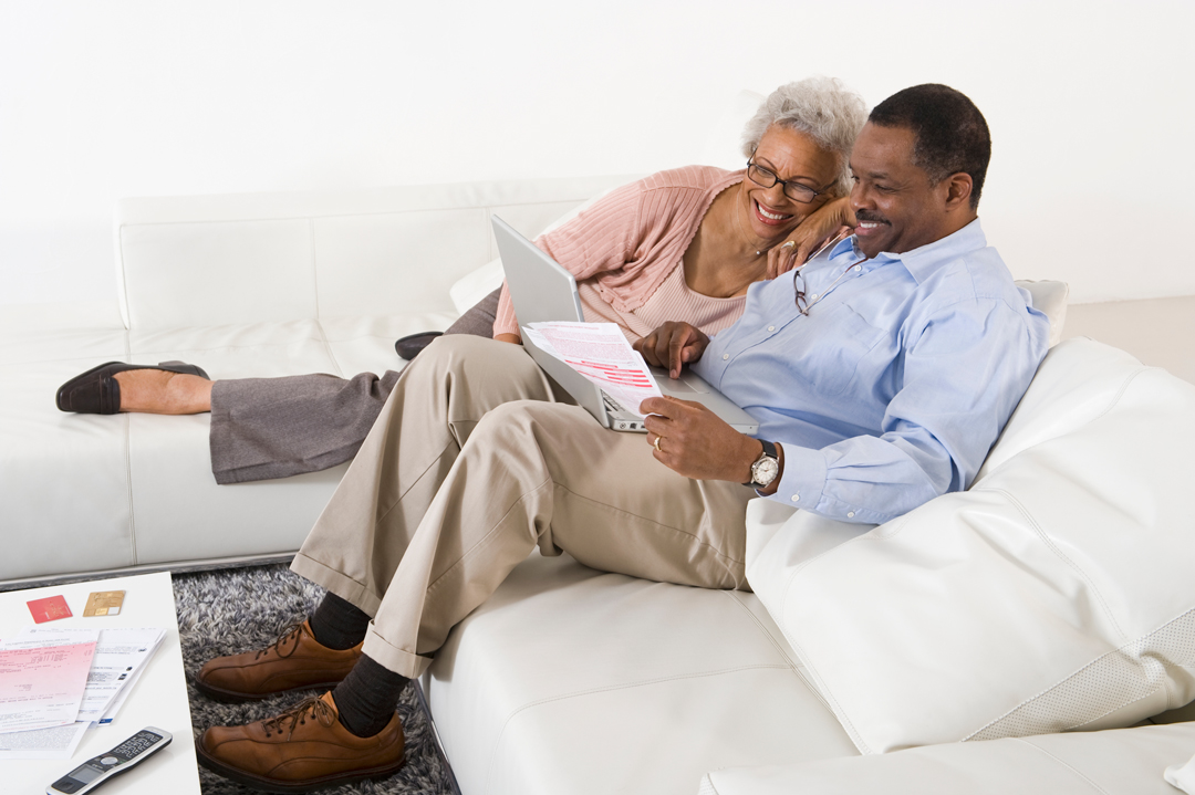 Cheerful senior couple sitting on couch and using laptop