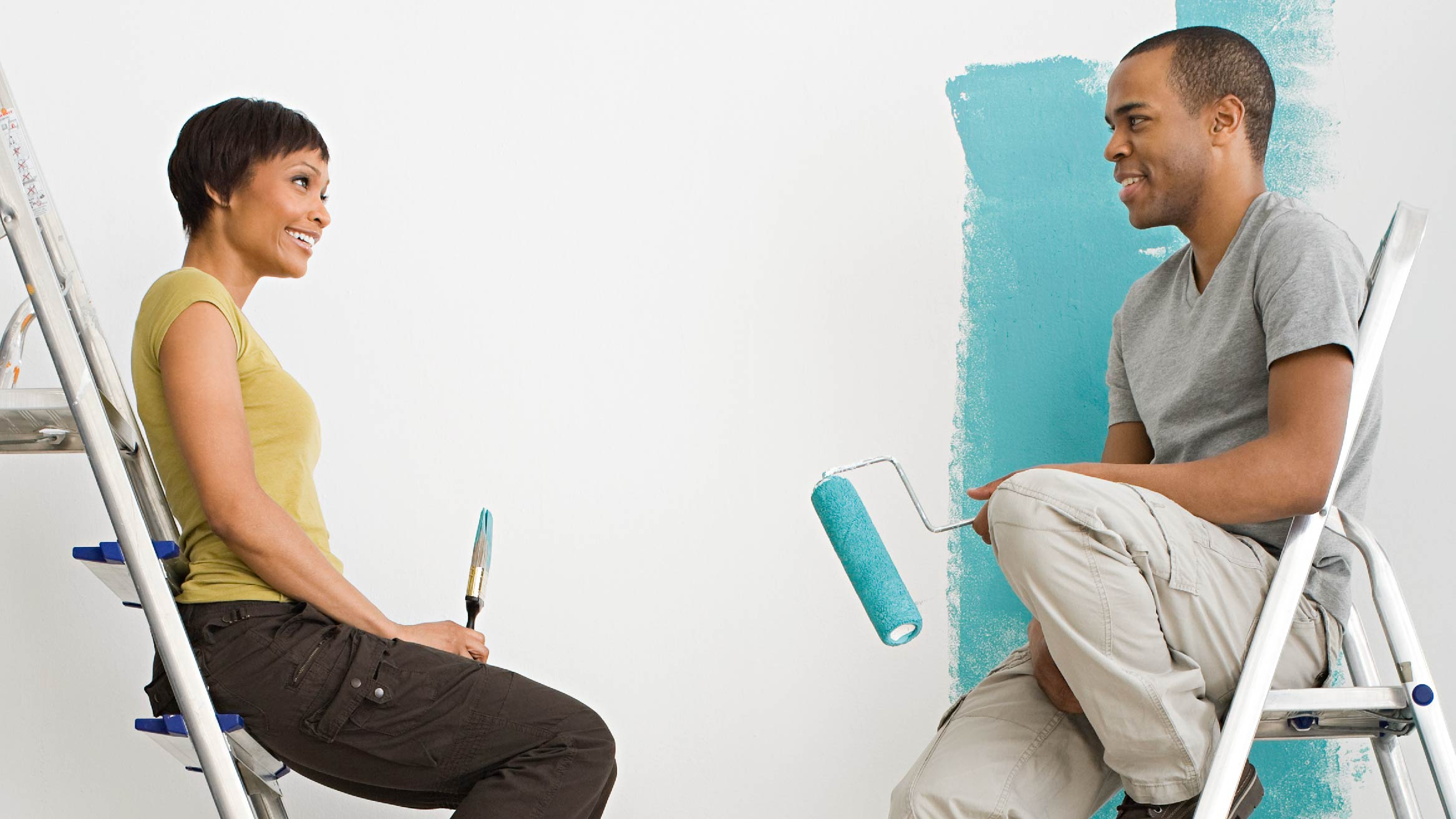 A couple sitting on ladders and taking a break from painting the wall.