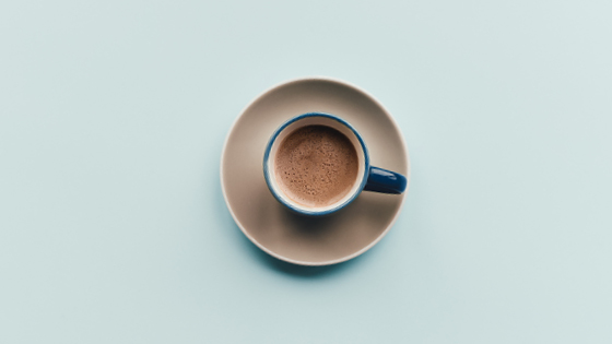 Aerial view of cup of coffee on light blue background