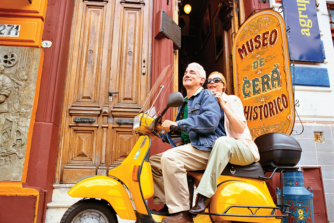 Senior man and woman riding their yellow scooter through the streets of Buenos Aires.