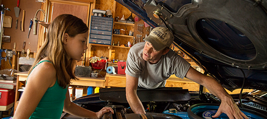 Father and daughter working on car in a garage