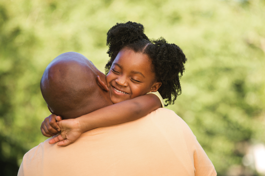 Young girl in pigtails hugs her father's neck