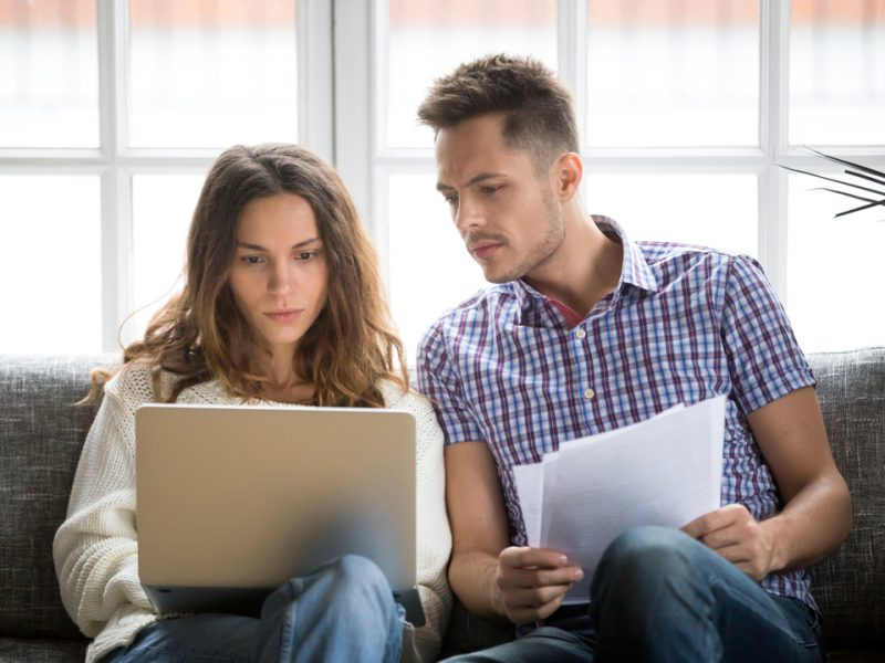 Young couple focused on laptop and holding bills.