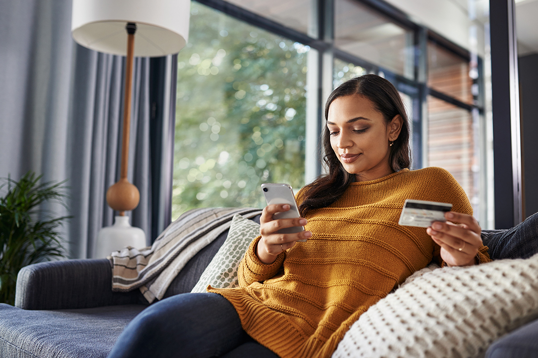 Young woman on her couch on her smartphone while holding a credit card