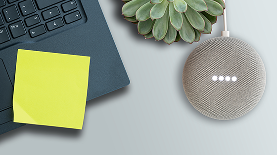 A smart voice device on a table with a laptop, plant and sticky note