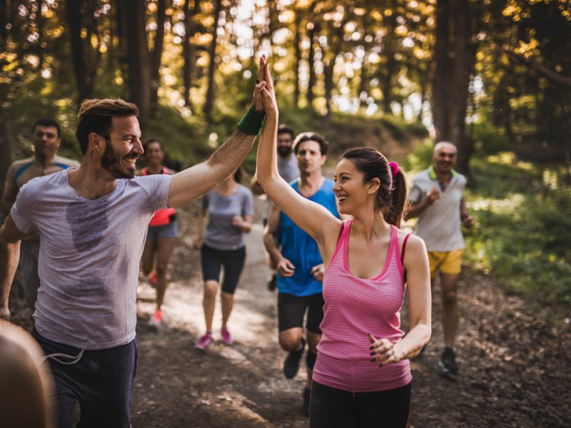 Man and woman high-fiving after a long run.