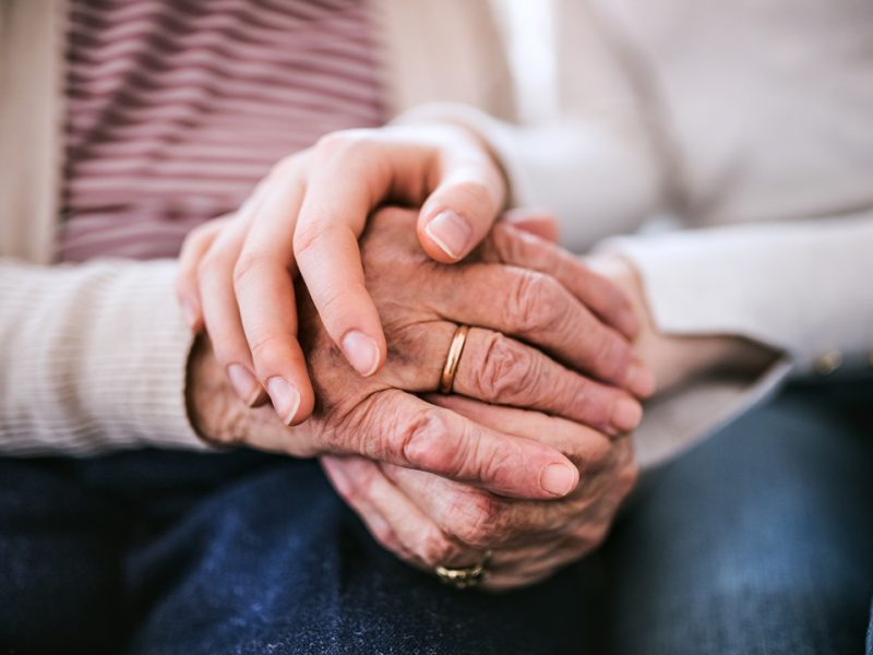 Close-up of clasped hands of elderly woman and young woman.
