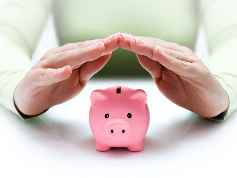 Woman in green top with her hands steepled over a pink piggy bank.