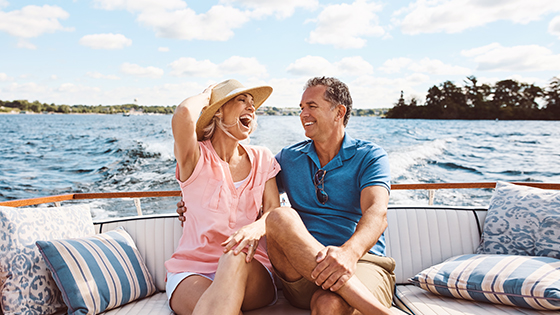 Man and woman sitting in boat laughing and enjoying life at the lake.