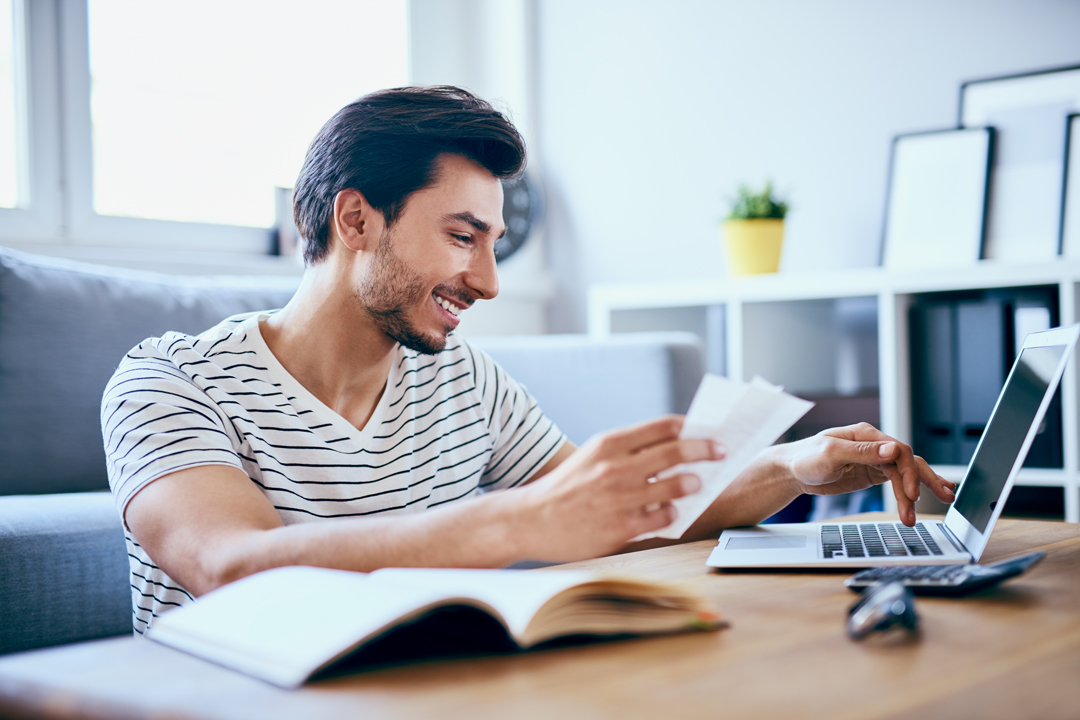 Happy man paying bills on his laptop in living room