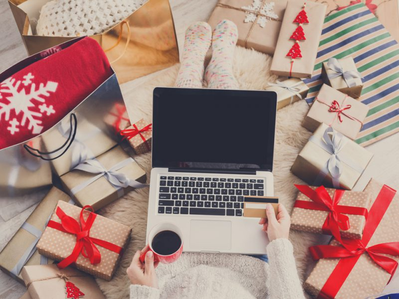 Woman drinking coffee and shopping online for the holidays
