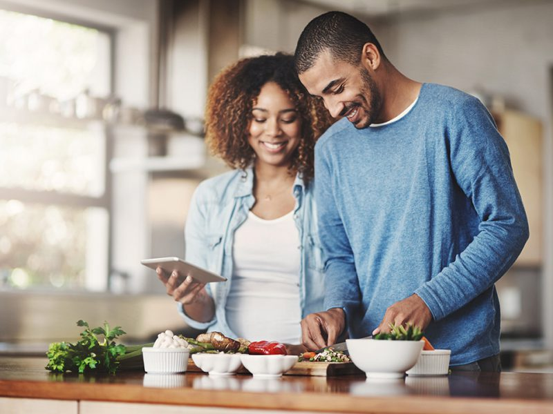 Young man and woman prepping food for dinner.