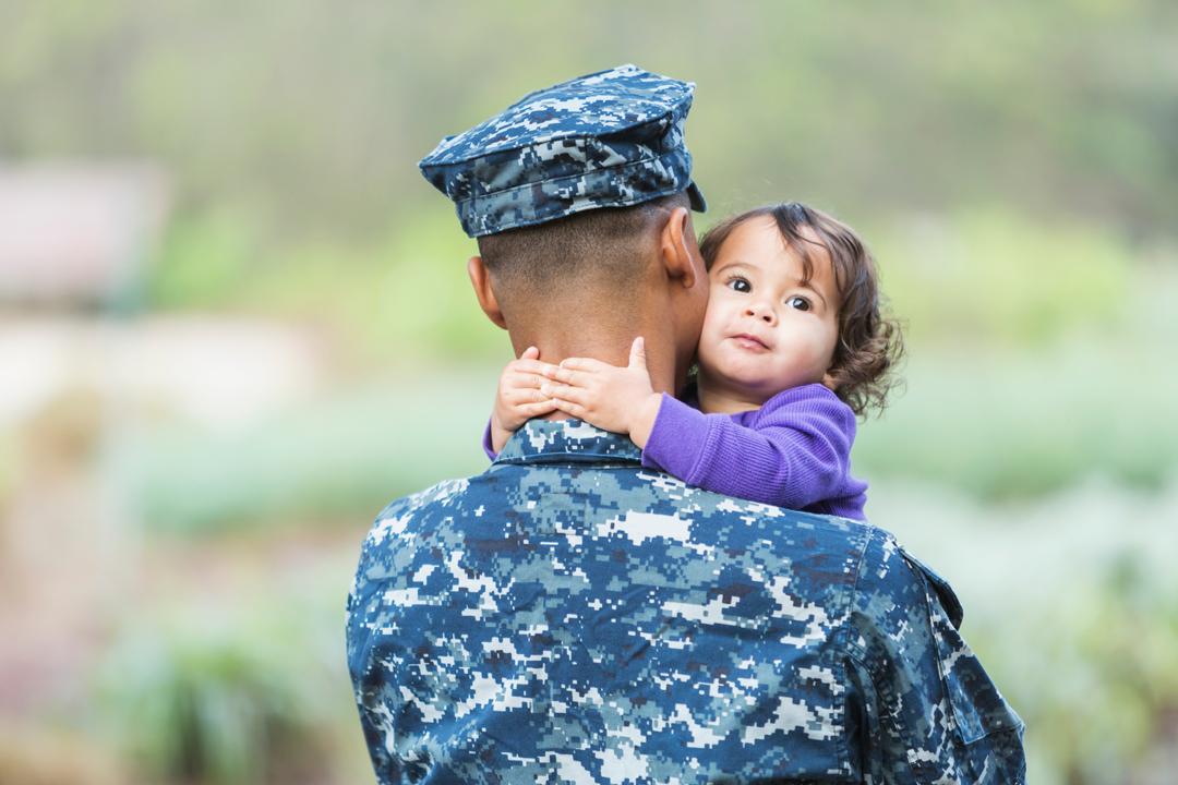 Man in uniform with little girl hugging his neck.