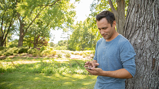 Man standing by a tree on his smartphone