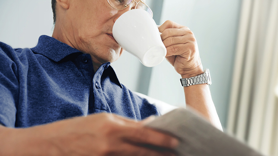 Close up of man in blue shirt drinking coffee.