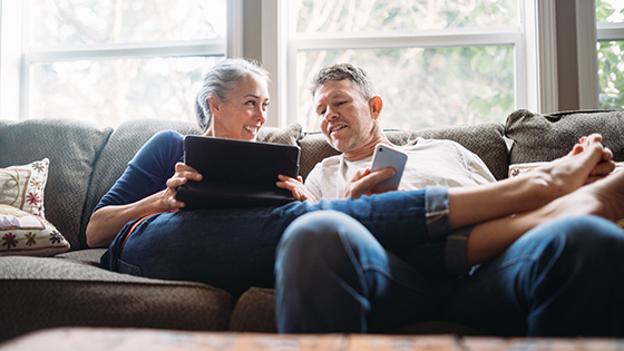 Couple relaxing on couch with one holding a tablet and one holding a smartphone.