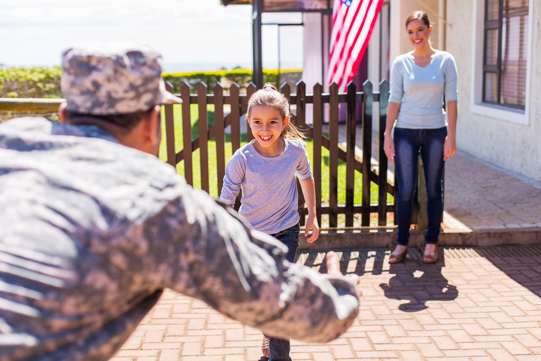 Military father being greeted by daughter and wife