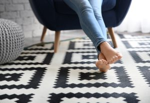 Woman sitting in a chair with feet on a black and white patterned rug.