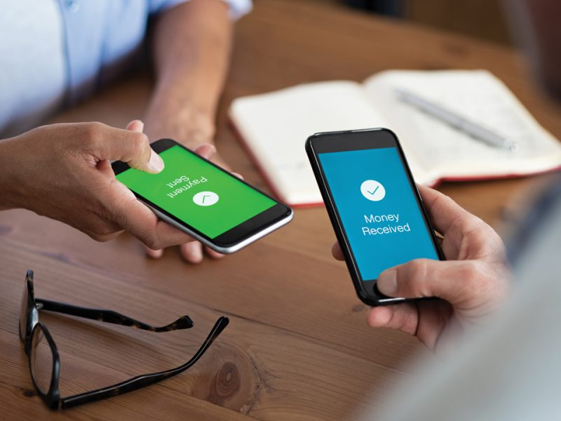 Close up of two peole paying each other using person to person payments