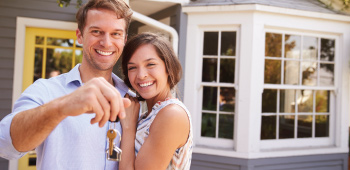 Young couple smiling in front of their home they just bought man holding keys