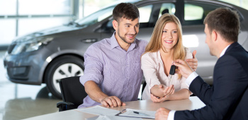 Couple at auto dealership buying a new sedan