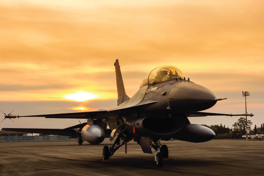 F16 Fighter jet on runway against sunset in background