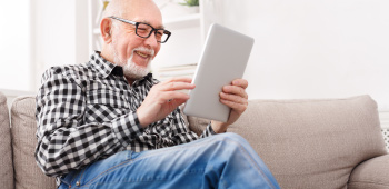 Older gentleman using tablet to check on his finances