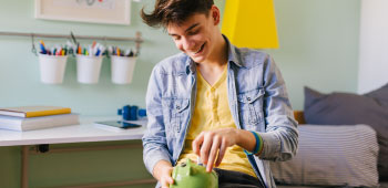 Teenage boy saving money for college in piggy bank