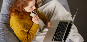 Young redhead adult female with laptop and credit card considering an online purchase
