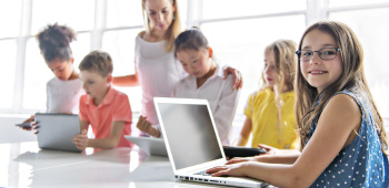 Young children using laptops and tablets supervised by adult