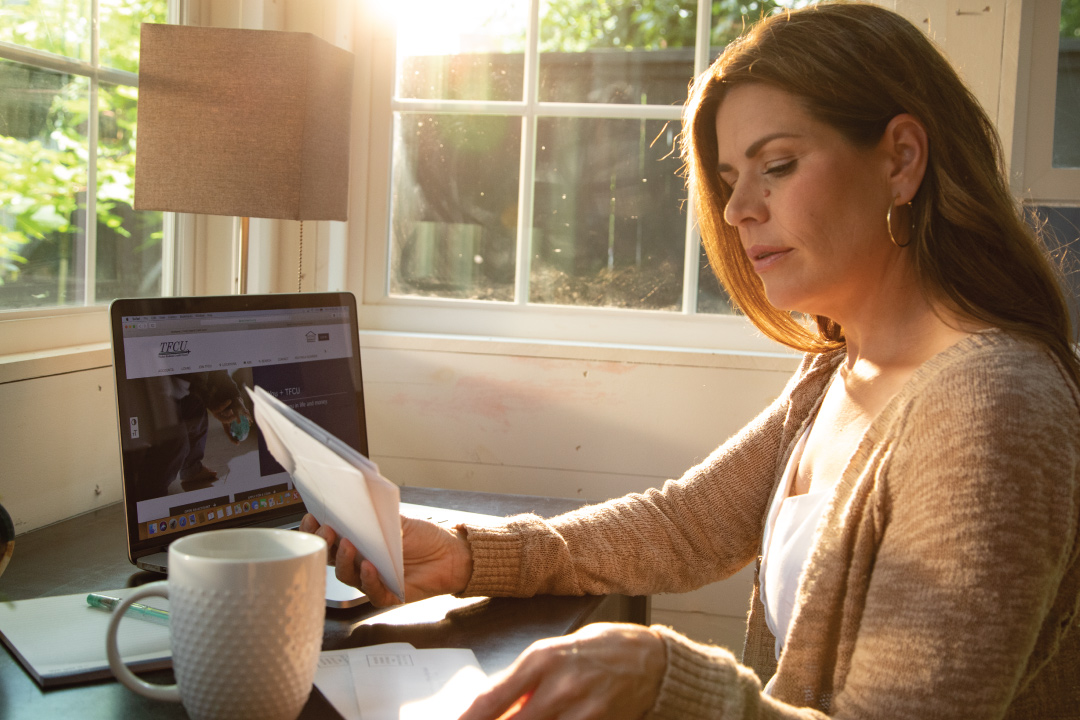 woman at desk with laptop paying bills with checks
