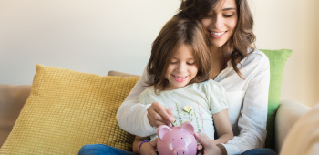 Mother holding young daughter and teaching her about money and placing change in a piggy bank