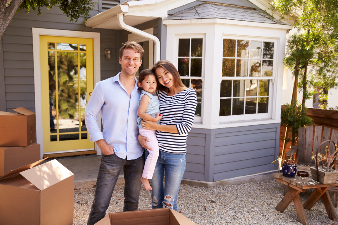 Smiling, young man and woman holding their daughter while standing in front of a new home surrounded by moving boxes.