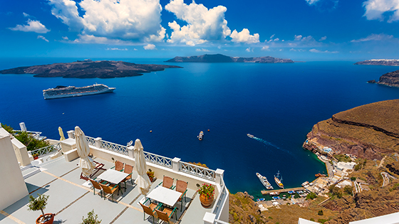 Beautiful ocean view from balcony in Greece with cruise ship in the distance.