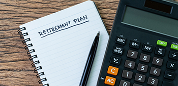 Retirement planning on a notebook with a pen and calculator