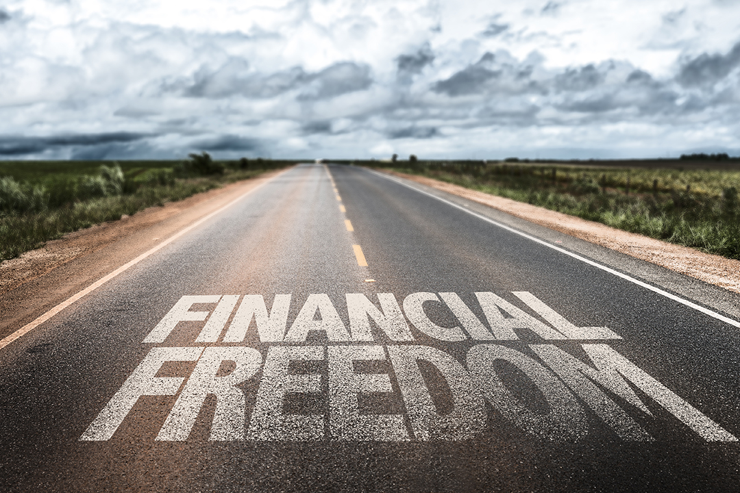 Highway with the words Financial Freedom spelled in bold letters on the pavement