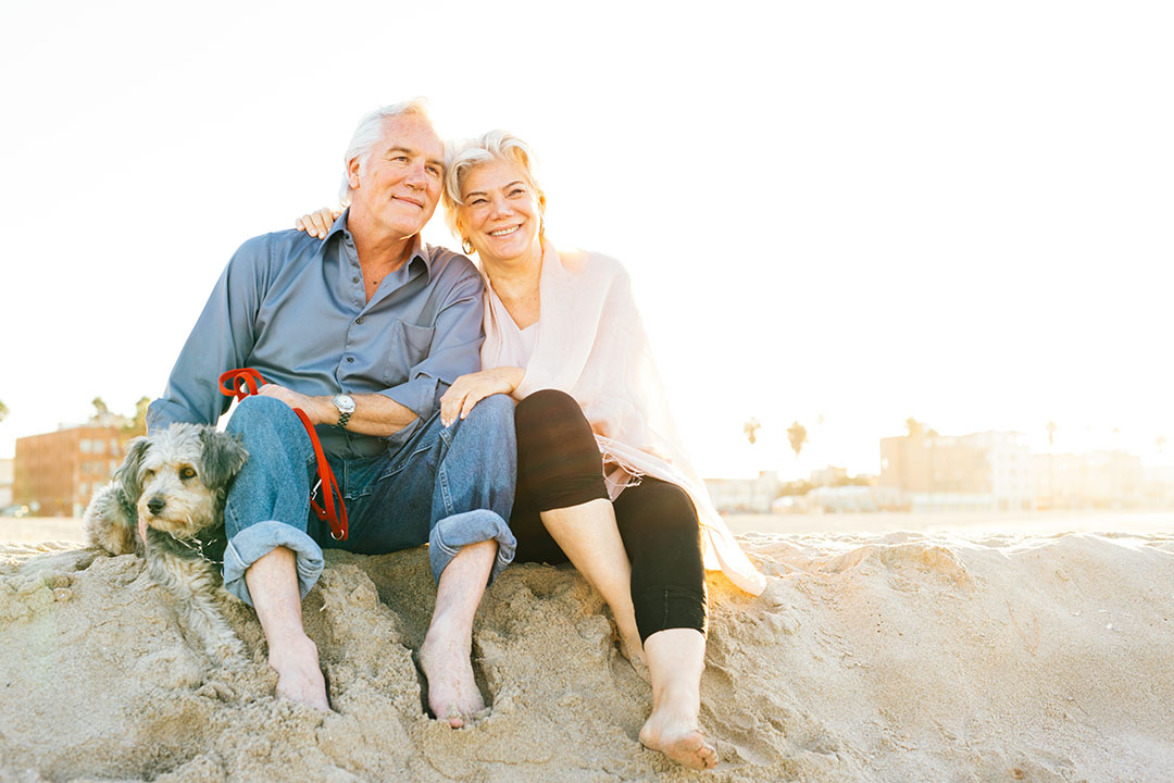 Senior couple sitting on the beach with dog.