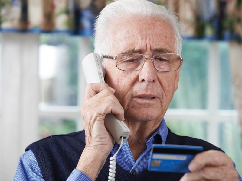 Senior man making a credit card payment over the phone.
