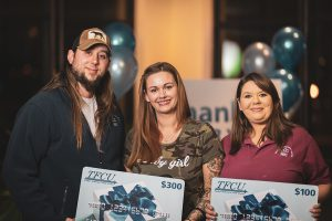A man and two women who are TFCU members are holding two TFCU gift card signs.
