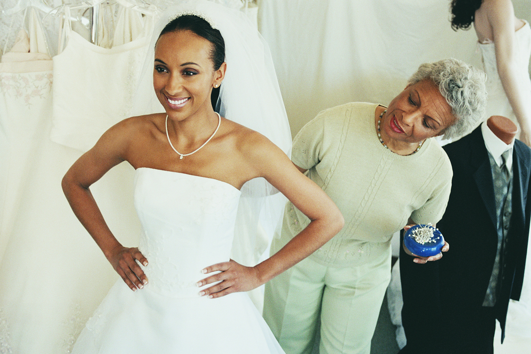 Young woman trying on white wedding dress, while older woman helps her with the dress fitting.
