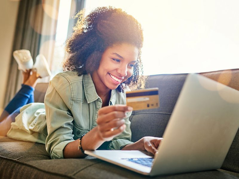 A young women lying on the couch at home while on her laptop and holding a card.