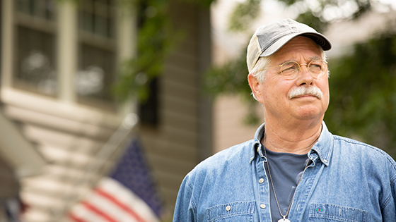 An older man looking out into the distance with an american flag in the back
