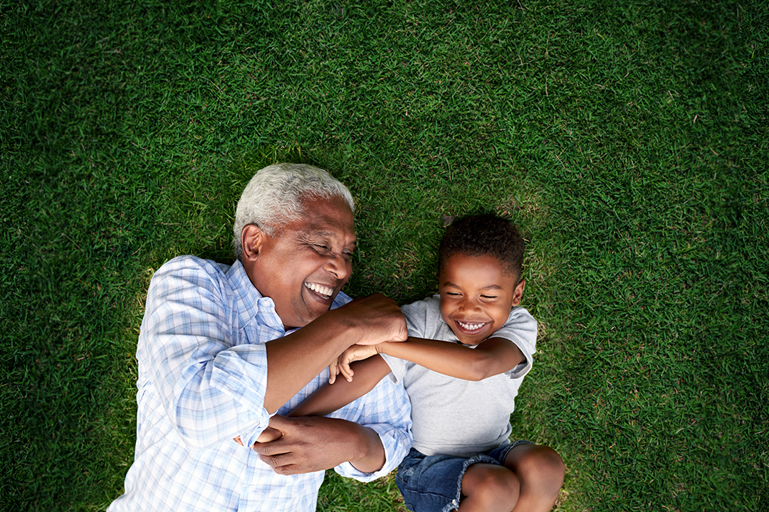 Grandfather and grandson playing and laughing in grass.